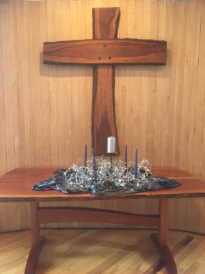 "The wooden altar table holds four dark blue tapers surrounding a large white pillar candle on a dark velvelt cloth with an unruly bundle of starry wire serving as the Advent ""wreath"""