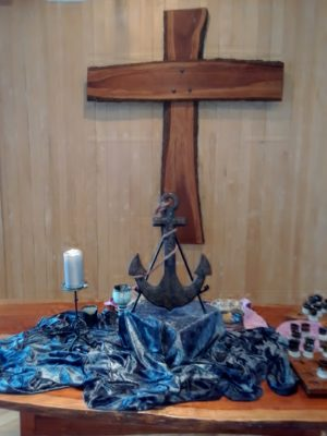 The altar with an anchor, shiny blue cloth, and communion cups